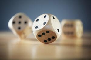 Rolling three dice on a wooden desk